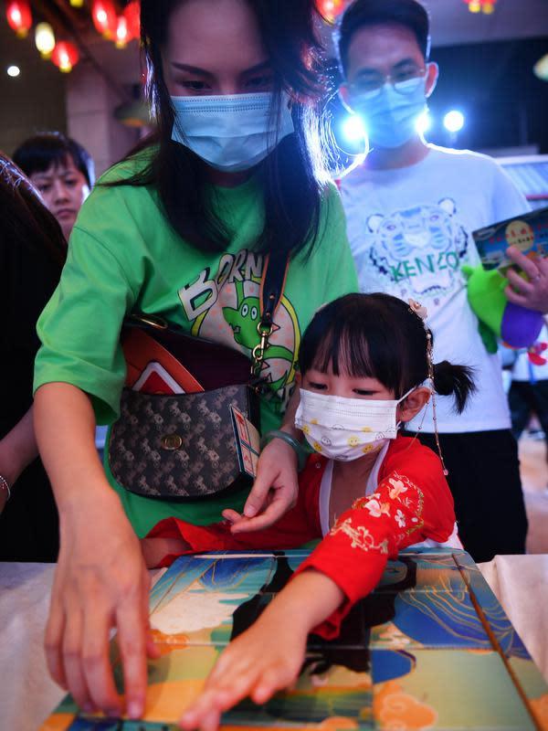 Seorang anak didampingi orang tua bermain puzzle dalam acara perayaan Festival Pertengahan Musim Gugur di Museum Hainan, Haikou, ibu kota Provinsi Hainan, China selatan (1/10/2020). (Xinhua/Guo Cheng)