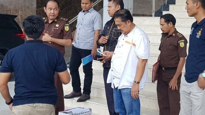 Tersangka korupsi di Riau menunggu mobil tahanan untuk dibawa ke rutan setelah diperiksa jaksa di Kejati Riau. (Liputan6.com/M Syukur)