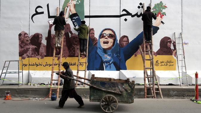 Seniman Afghanistan menggambar mural pada pagar Kementerian Urusan Perempuan saat memperingati Hari Perempuan Internasional di Kabul, Jumat (8/3). (AP Photo/Rahmat Gul)