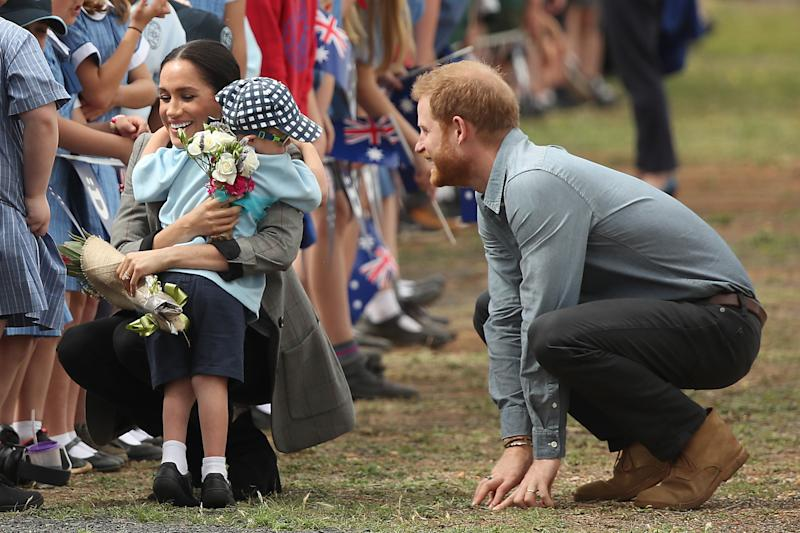 Meghan gives young fan, five-year-old Luke Vincent, a sweet hug as Harry watches on. Photo: Getty, meghan markle prince harry dubbo, meghan markle prince harry australia, meghan markle serena williams jacket, meghan markle pregnant