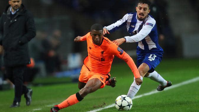Pemain Liverpool, Georginio Wijnaldum berebut bola dengan pemain FC Porto, Alex Telles dalam leg pertama babak 16 besar Liga Champions di Stadion Do Dragao, Kamis (15/2). Liverpool sukses menundukkan Porto dengan skor 5-0. (AP/Luis Vieira)