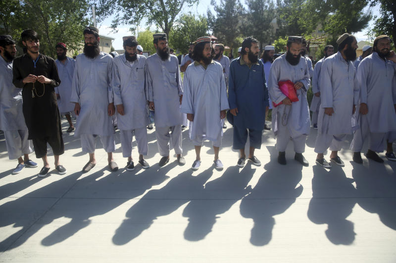 Afghan Taliban prisoners line up after their release from Bagram Prison in Parwan province, Afghanistan, Tuesday, May 26, 2020. The Afghan government freed hundreds of prisoners, its single largest prisoner release since the U.S. and the Taliban signed a peace deal earlier this year that spells out an exchange of detainees between the warring sides. (AP Photo/ Rahmat Gul)
