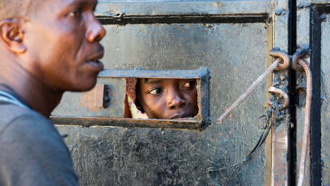 Ibu dari seorang anak yang tinggal di Panti Asuhan Church of Bible Understanding melihat melalui celah kecil di pintu masuk ketika mencari tahu kondisi setelah kebakaran di pinggiran Port-au-Prince di ibu kota Haiti, Jumat (14/2/2020). Lima belas anak tewas dalam kebakaran. (AP/Dieu Nalio Chery)