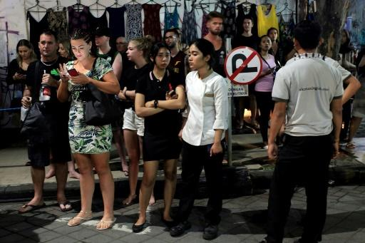Foreign tourists and hotel staff stand on the street afer being evacuated in Bali's capital Denpasar on Sunday night