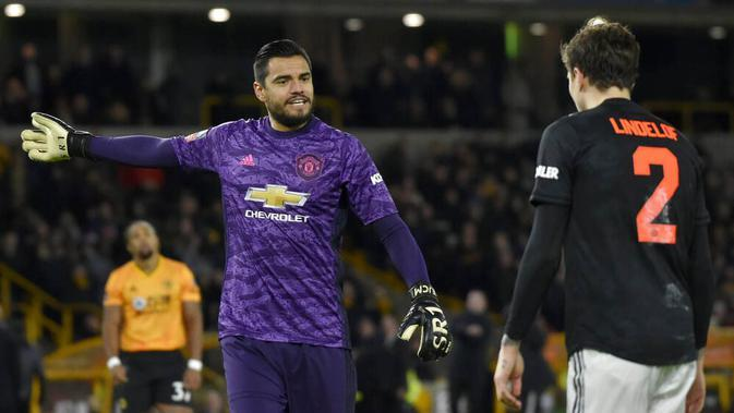 Kiper Manchester United, Sergio Romero, berbincang dengan Victor Lindelof saat melawan Wolverhampton Wanderers, Romain Saiss, pada laga Piala FA di Stadion Molineux, Sabtu (4/1/2020). Kedua tim bermain imbang 0-0. (AP/Rui Vieira)