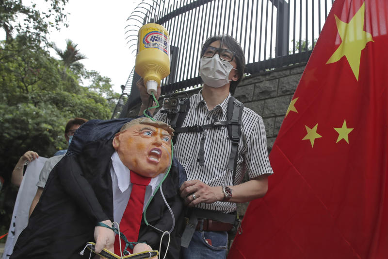 Pro-China supporters hold the effigy of U.S. President Donald Trump and Chinese national flag outside the U.S. Consulate during a protest in Hong Kong, Saturday, May 30, 2020. President Donald Trump has announced a series of measures aimed at China as a rift between the two countries grows. He said Friday that he would withdraw funding from the World Health Organization, end Hong Kong's special trade status and suspend visas of Chinese graduate students suspected of conducting research on behalf of their government. (AP Photo/Kin Cheung)