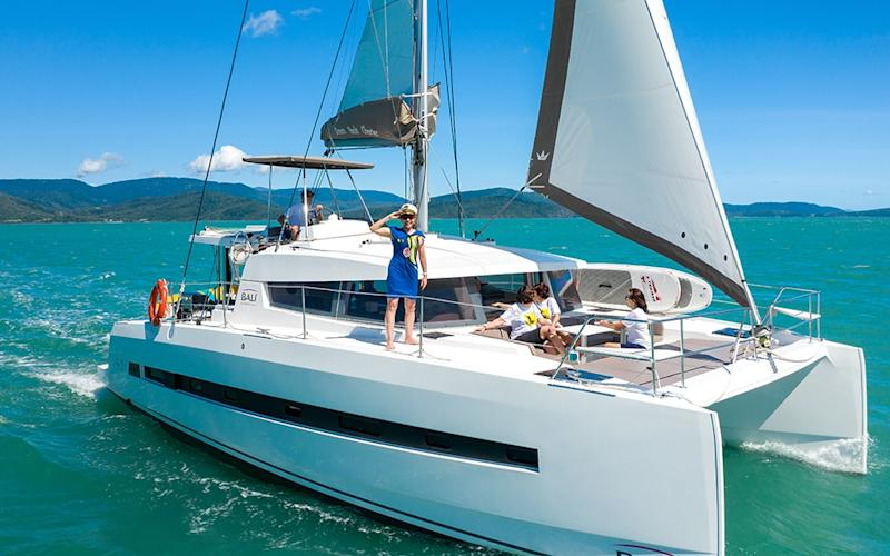Kathy Lette takes some pointers from the captain after setting sail from Airlie Beach