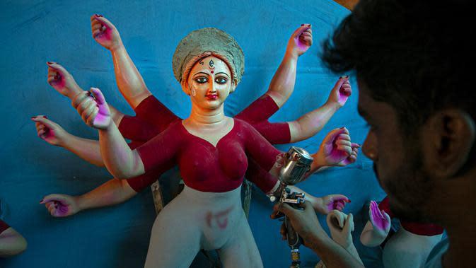 Seniman membuat patung Dewi Durga jelang Festival Durga Puja di Gauhati, India, Jumat (16/10/2020). Para pejabat kesehatan memperingatkan tentang potensi penyebaran COVID-19 selama musim festival keagamaan dengan pertemuan besar di kuil dan distrik perbelanjaan. (AP Photo/Anupam Nath)
