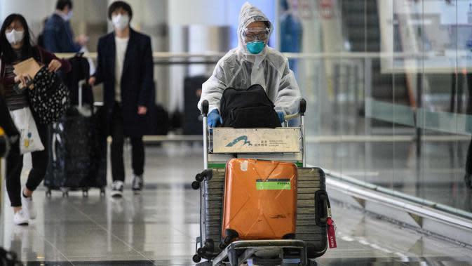 Penumpang mengenakan pakaian pelindung saat tiba di Bandara Internasional Hong Kong, Hong Kong (19/3/2020). Covid-19 yang menginfeksi lebih dari 200.000 orang terus menimbulkan kekhawatiran. (AFP/Anthony Wallace)