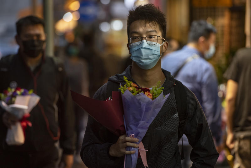HONG KONG, CHINA - FEBRUARY 14, 2020: Customers carry flowers during Valentine's Day wearing a face mask as a preventative measure against the COVID-19. As of Friday, the death toll from China's coronavirus virus epidemic surpassed 1,400 and 60,000 infected after new reporting methods were adopted.- PHOTOGRAPH BY Miguel Candela / Echoes Wire/ Barcroft Media (Photo credit should read Miguel Candela / Echoes Wire/Barcroft Media via Getty Images)