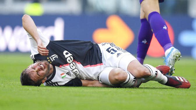 Gelandang Juventus, Miralem Pjanic, terjatuh saat berebut bola dengan pemain Fiorentina pada laga Serie A di Stadion Allianz, Minggu (2/2/2020). Juventus menang 3-0 atas Fiorentina. (AP/Fabio Ferrari)