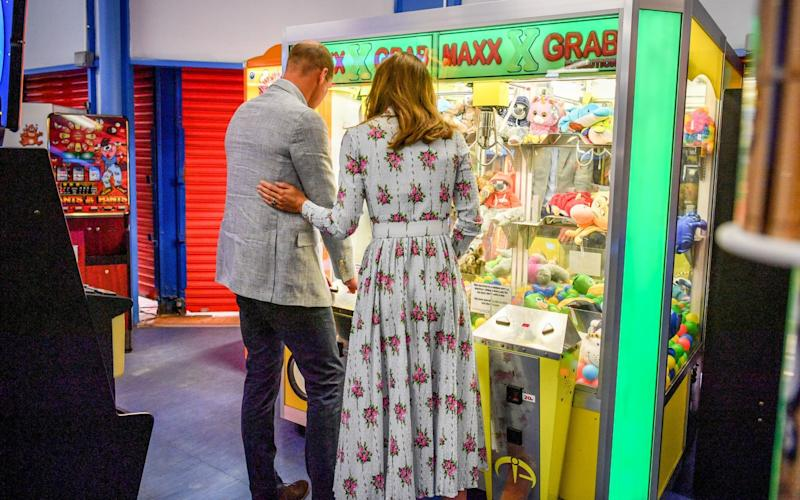 The Duchess of Cambridge tenderly touches her husband's back during a 'grab a teddy' game in the arcade - Ben Birchall/PA