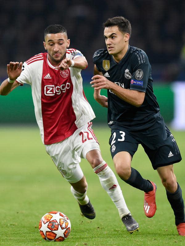 Gelandang Ajax, Hakim Ziyech berebut bola dengan bek Real Madrid, Sergio Reguilon pada leg pertama 16 besar Liga Champions di Johan Cruijff ArenA, Rabu (13/2). Real Madrid harus bersusah payah menaklukkan Ajax dengan skor tipis 2-1. (JOHN THYS / AFP)