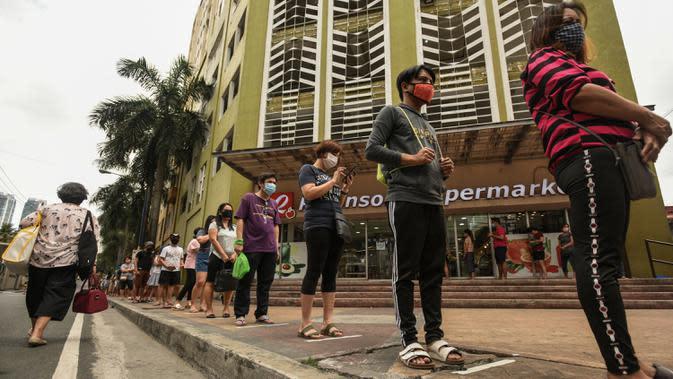 Pembeli berdiri dengan jarak yang aman di garis antrean yang ditempatkan di luar supermarket di Manila, Filipina, Selasa (17/3/2020). Hingga Rabu siang, terdapat 187 positif Virus Corona Covid-19 di Filipina, dengan 12 orang meninggal dan lima orang sembuh. (Maria TAN / AFP)