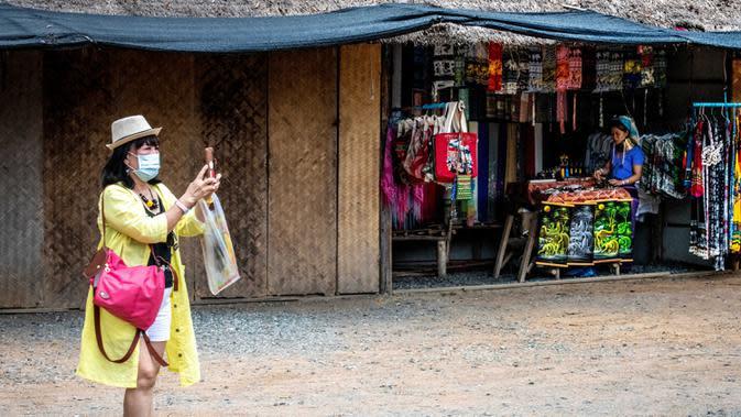 Seorang turis yang mengenakan masker mengambil gambar di luar kios suvenir di Taman Chang Siam, Pattaya, Thailand, Rabu (12/2/2020). Chang Siam Park adalah salah satu primadona bagi wisatawan China di Pattaya yang kini berangsur sepi karena penyebaran virus corona covid-19. (Mladen ANTONOV / AFP)