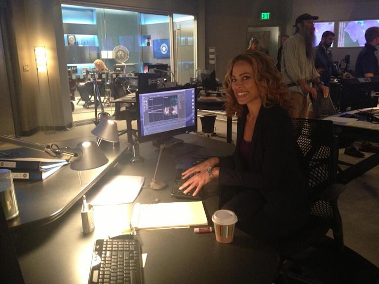 Tawny is all smiles while sitting at her desk, something her character rarely does! #Unforgettable premieres Sunday!