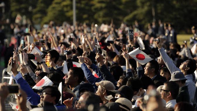 Ribuan warga mengabadikan parade Kaisar Naruhito dan Permaisuri Masako di Tokyo, Jepang, Minggu (10/11/2019). Diperkirakan sebanyak puluhan ribu warga memadati rute yang dilalui Kaisar Naruhito dan Permaisuri Masako. (AP Photo/Jae C. Hong)