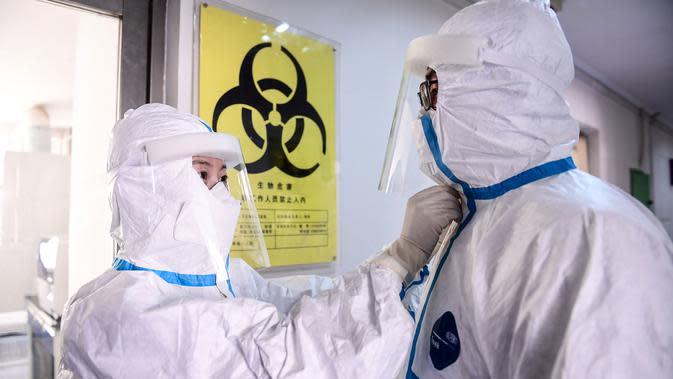 Petugas laboratorium membantu rekannya melepaskan pakaian pelindung di sebuah laboratorium di Shenyang, provinsi Liaoning timur laut China, Rabu (12/2/2020). Per hari ini, Rabu (12/2) tercatat korban meninggal dunia akibat virus corona di China tercatat mencapai 1.110. (STR/AFP)