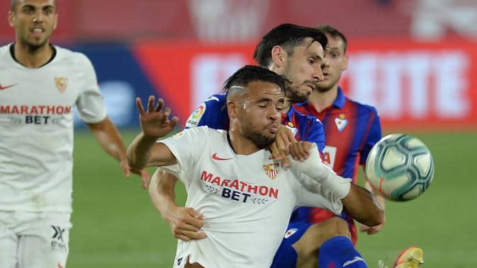Penyerang Sevilla, Youssef En-Nesyri, berebut bola dengan bek Eibar, Paulo Oliveira, pada laga lanjutan La Liga pekan ke-34 di Estadio Ramon Sanchez Pizjuan, Selasa (7/7/2020) dini hari WIB. Sevilla menang 1-0 atas Eibar. (AFP/Cristina Quicler)