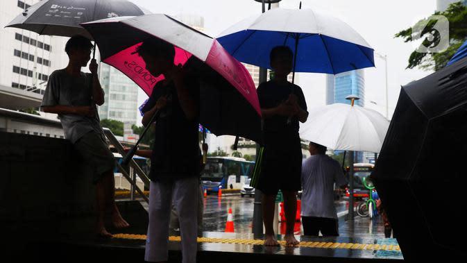 Anak-anak menawarkan jasa ojek payung di tengah hujan yang turun di kawasan Bundaran HI, Jakarta, Senin (3/2/2020). Hujan deras yang mengguyur sejumlah wilayah di DKI Jakarta dimanfaatkan para pengojek payung untuk mencari penghasilan tambahan. (Liputan6.com/Angga Yuniar)