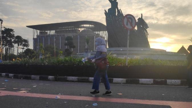 Seorang mahasiswa memungut sampah di jalan usai demo tolak Omnibus Law. (Liputan6.com/M Syukur)