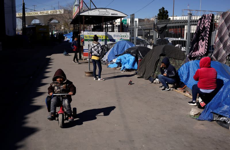 Mexican asylum seekers, who are camping near the Paso del Norte international border crossing bridge while waiting to apply for asylum to the U.S., stand outside their tents in Ciudad Juarez