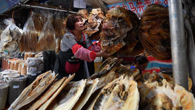 Penjual menata makanan laut kering di sebuah pasar di Kota Haikou, Provinsi Hainan, China, Rabu (15/1/2020). Warga Haikou akhir-akhir ini sibuk berbelanja untuk menyambut Tahun Baru Imlek 2020. (Xinhua/Guo Cheng)