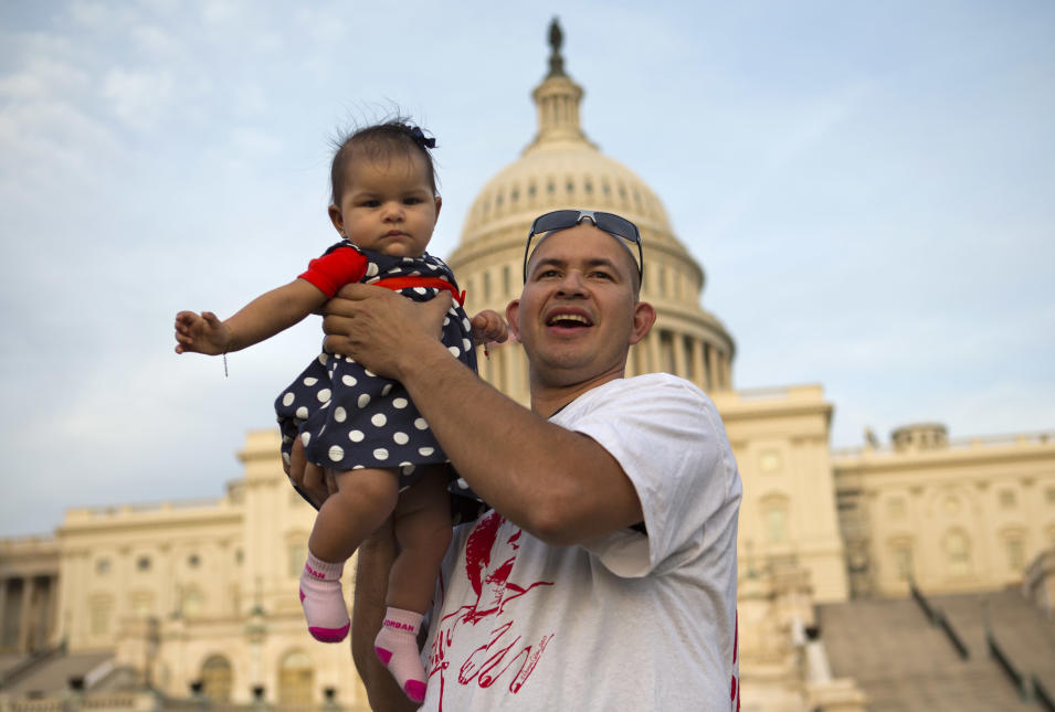 """Edwin Munoz, who is originally from El Salvador, holds his daughter Jocelyn Munoz, 5 months, up for a portrait at the end of the """"Rally for Citizenship,"""" a rally in support of immigration reform, on Capitol Hill in Washington, on Wednesday, April 10, 2013. Bipartisan groups in the House and Senate are said to be completing immigration bills that include a pathway to citizenship for the nation's 11 million immigrants with illegal status. """"We have to give papers to all the immigrants who came here to work,"""" says Munoz, """"we're not terrorists we're workers."""" (AP Photo/Jacquelyn Martin)"""