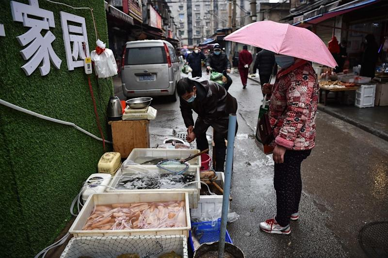 A masked vendor sells fish and turtles at a market in Wuhan where the coronavirus was discovered January 24 2020. — AFP pic