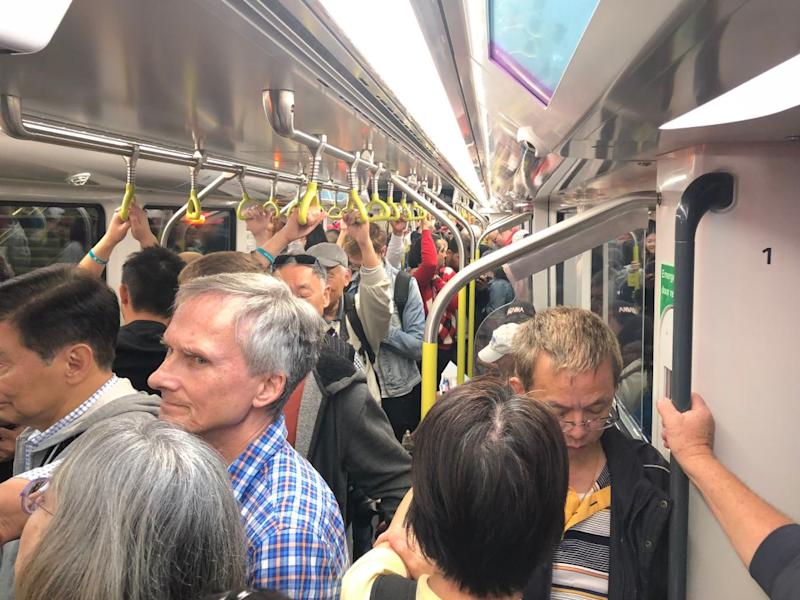 Metro Trains Sydney commuters appear to be squished together in a packed carriage.