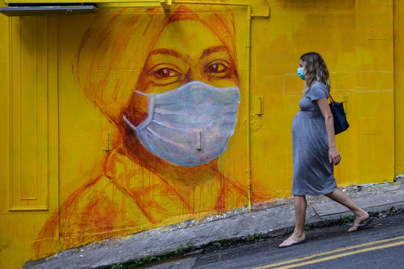 TOPSHOT - A pregnant woman wearing a face mask as a precautionary measure walks past a street mural in Hong Kong, on March 23, 2020, after the citys Chief Executive announced plans to temporarily ban the sale of alcohol in bars and restaurants as a measure to help stop the spread of the COVID-19 caused by the novel coronavirus. - Hong Kong will ban all non-residents from entering the city from midnight on March 24, 2020 in a bid to halt the coronavirus, its leader says, as she unveils plans to stop restaurants and bars serving alcohol. (Photo by ANTHONY WALLACE / AFP) (Photo by ANTHONY WALLACE/AFP via Getty Images)