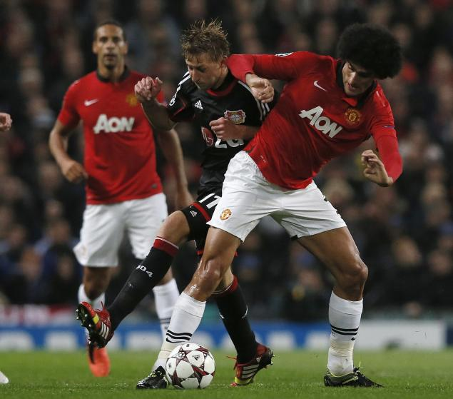 Manchester United's Fellaini challenges Bayer Leverkusen's Boenisch for the ball during their Champions League soccer match at Old Trafford in Manchester