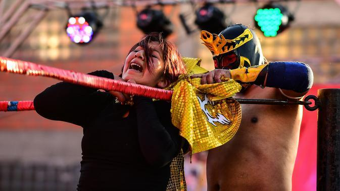Pegulat Bolivia, Blanca Perez dikunci oleh lawannya pegulat pria di atas ring gulat di El Alto, pada 24 November 2019. Di Bolivia ada sebuah atraksi gulat yang diperankan perempuan dengan menggunakan busana khas warga Bolivia. (Ronaldo SCHEMIDT / AFP)
