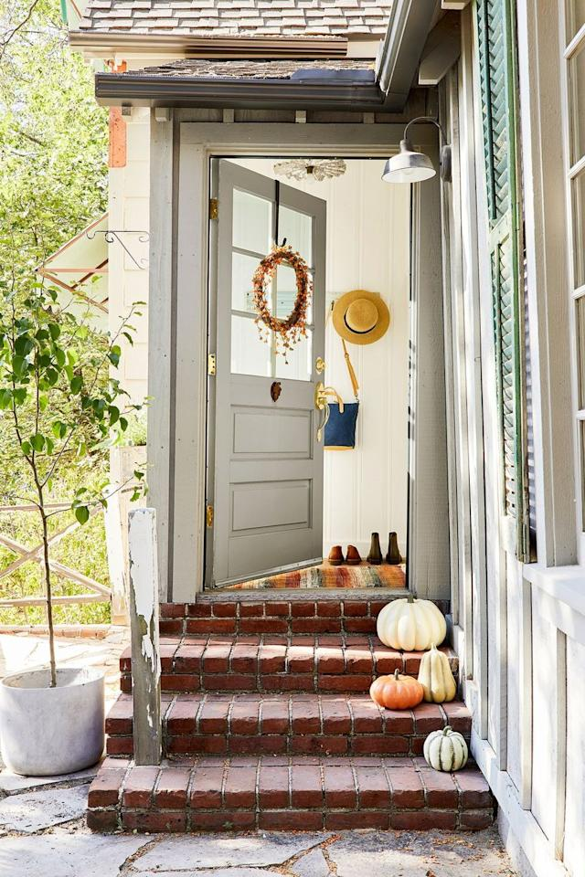 <p>Opt for a fall-friendly runner or welcome mat by the door instead of the one you used all summer. And bonus points if you line the front steps with pumpkins that reflect the orange beaded wreath on the door. </p>