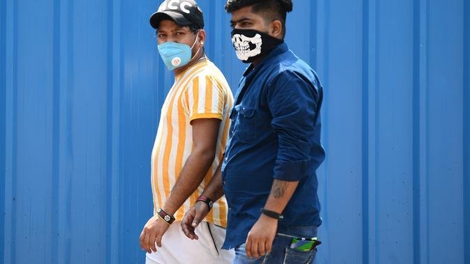 Dua pria mengenakan masker berjalan di sepanjang jalan di New Delhi (16/9/2020). Total kasus Covid-19 di India melampaui lima juta pada 16 September, data kementerian kesehatan menunjukkan Pandemi meluas cengkeramannya di negara tersebut. (AFP/Sajjad Hussan)