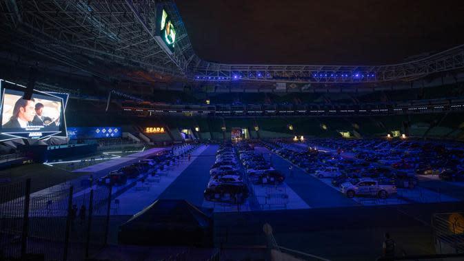 Orang-orang menonton film dari dalam mobil mereka di drive in yang dipasang di stadion sepak bola Palmeiras di Sao Paulo, Brasil, Kamis (25/6/2020). Stadion yang dapat menampung hingga 300 mobil tersebut berubah fungsi menjadi lokasi bioskop drive ini di masa pademi Covid-19. (AP Photo/Andre Penner)