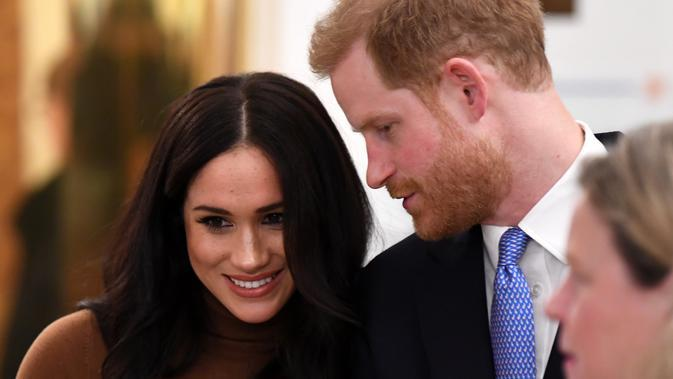 Meghan Markle dan Pangeran Harry menghadiri acara di Kedutaan Besar Kanada sebelum menyatakan mundur dari status bangsawan senior Kerajaan Inggris. (dok. Adrian DENNIS/AFP)