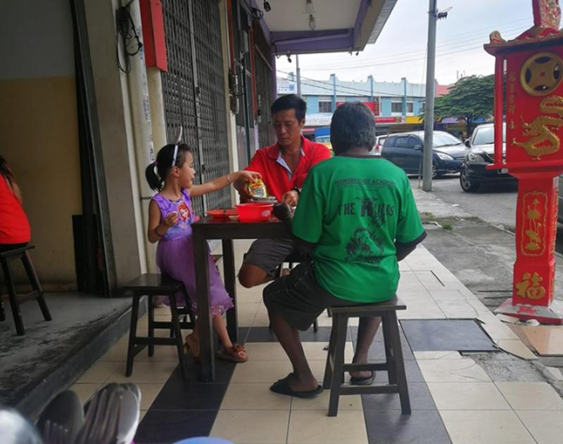 A father and daughter are pictured having a meal of bak kut teh with a man who appeared to be homeless. — Picture from Facebook/ Willy Chong