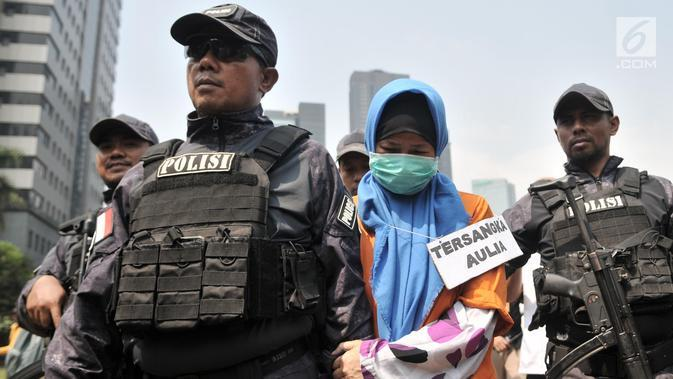 Tersangka Aulia Kesuma (tengah) digiring polisi saat dihadirkan dalam kasus istri bunuh dan bakar suami serta anak tiri di Polda Metro Jaya, Jakarta, Senin (9/9/2019). Aulia dan model yang memerankan tersangka Kelvin memeragakan tiga adegan pembakaran korban dalam mobil. (merdeka.com/Iqbal Nugroho)