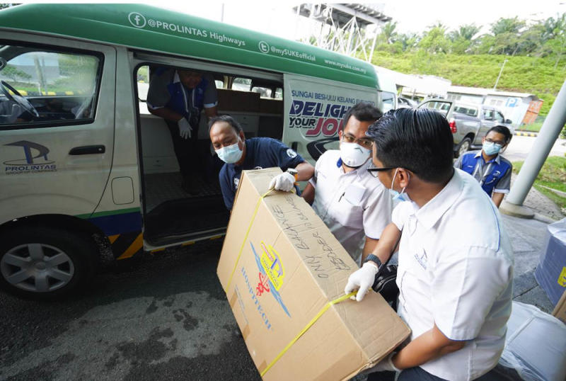Members of the Prolintas team transporting medical equipment to be used by hospitals overwhelmed with Covid-19 infected patients. — Picture courtesy of Prolintas