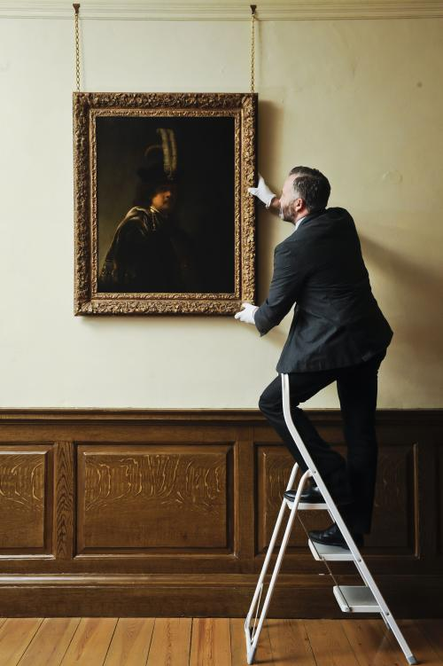 Curator of Pictures and Sculpture at Buckland Abbey David Taylor adjusts the newly confirmed self-portrait by Rembrandt discovered at Devonshire Abbey, in Skipton, England, in this photo dated Wednesday March 13, 2013. The masterpiece was gifted in 2010 to Britain's National Trust by the family estate of a wealthy property developer, and has now undergone detailed investigations led by the world's leading Rembrandt expert, Ernst van de Wetering, to determine its provenance before declaring it an original painting by the Dutch master. The painting is now valued at 20 million pounds (US dlrs 30 million) and will be hung at Buckland Abbey for a few months before being sent for cleaning and further expert analysis including x-ray and tree-ring dating of the beech panel it is painted on. (AP Photo/Ben Birchall, PA) UNITED KINGDOM OUT - NO SALES - NO ARCHIVES