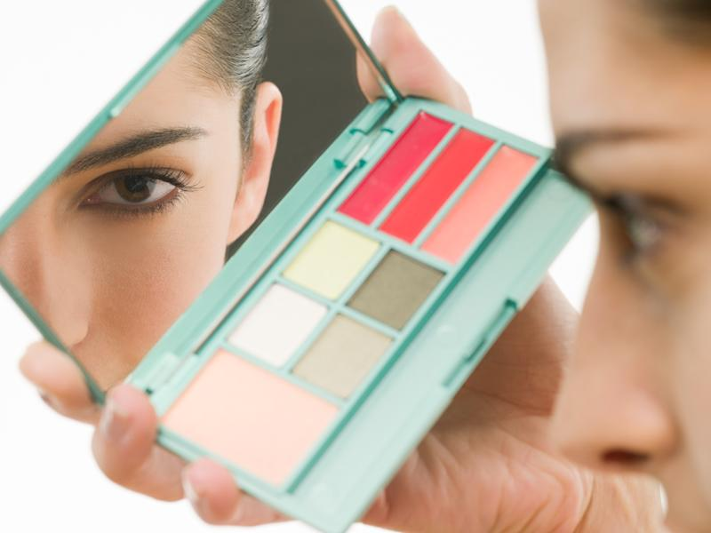 Woman with a makeup palette looking into the mirror
