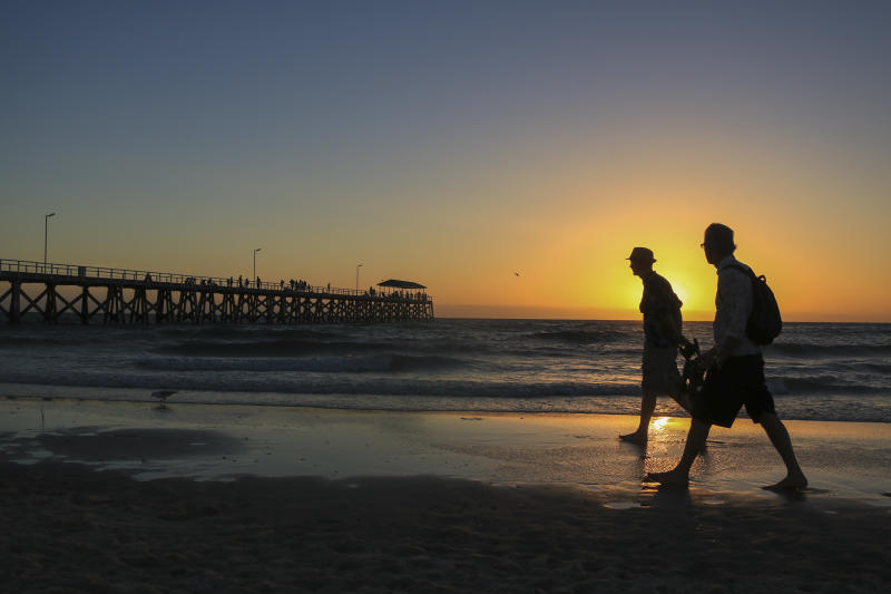 People walking on a beach with a jetty silhouetted against a setting sun in Adelaide, Australia.