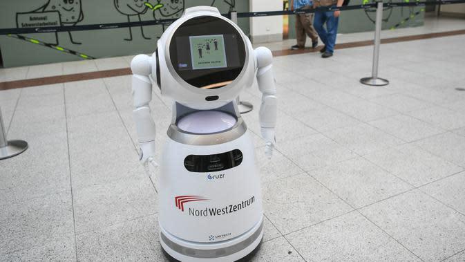 Para pengunjung berjalan melewati sebuah robot pintar yang menjelaskan tentang langkah-langkah pencegahan COVID-19 di sebuah pusat perbelanjaan di Frankfurt, Jerman, pada 12 September 2020. (Xinhua/Lu Yang)