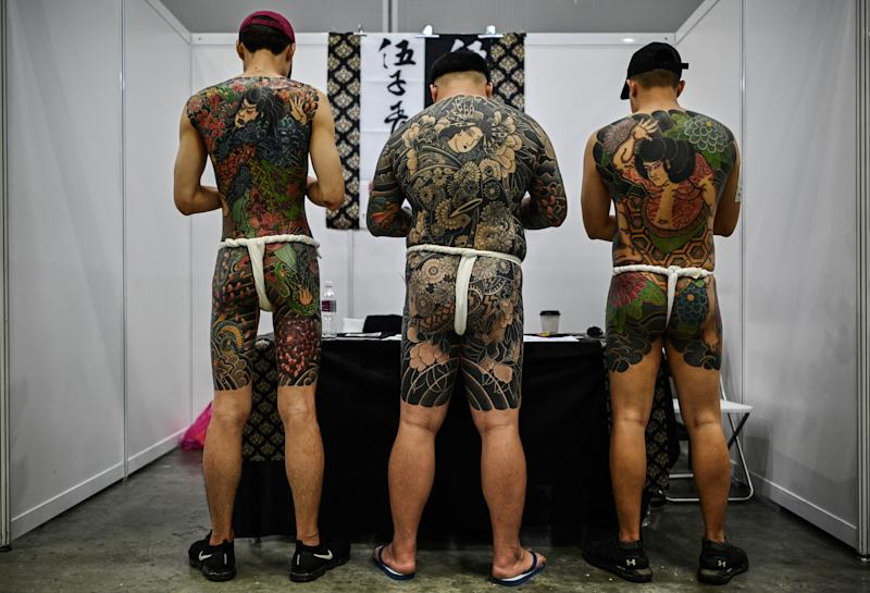 Three men display their tattoos during the International Malaysia Tattoo Expo in Kuala Lumpur on November 29, 2019. - The international tattoo expo is held for the first ime in Kuala Lumpur celebrating that art of tattoo and gathering over a hundred tattoo artists from 40 countries. (Photo by Mohd RASFAN / AFP) (Photo by MOHD RASFAN/AFP via Getty Images)