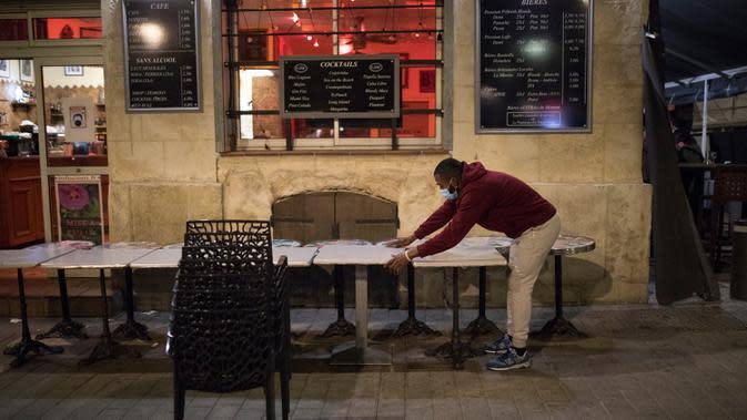 Seorang pramusaji menutup teras bar di Marseille, selatan Prancis, Minggu (27/9/2020). Restoran dan bar di Marseille pada hari Minggu bersiap tutup selama sepekan sebagai bagian dari pembatasan baru baru Covid-19. (AP Photo/Daniel Cole)