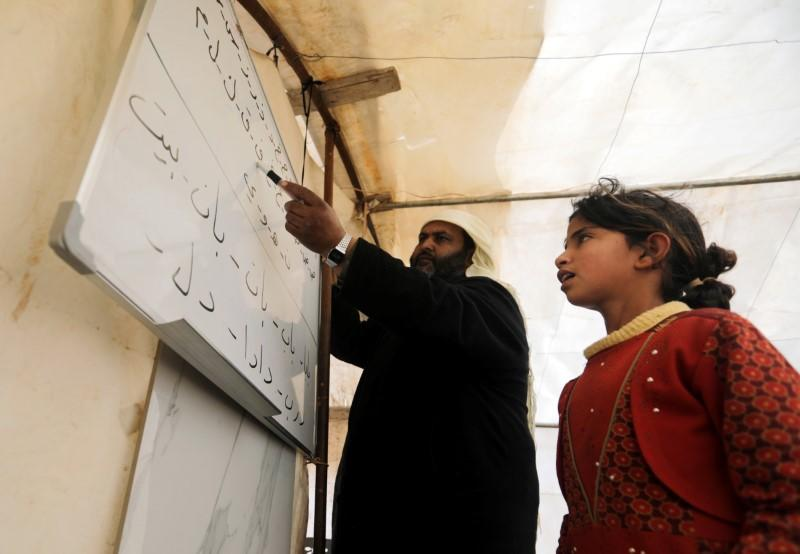 A student recites the Arabic alphabet at a makeshift school in a tent in Azaz