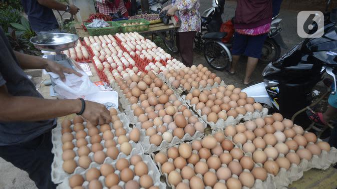 Pedagang telur melayani pembeli di pinggir jalan kasawan Perumahan Nusa Indah, Tangerang Selatan, Banten, Jumat (22/5/2020). Harga telur warna cokelat Rp 22 ribu per kilogram, sedangkan telur warna putih Rp 20 ribu per kilogram. (merdeka.com/Dwi Narwoko)