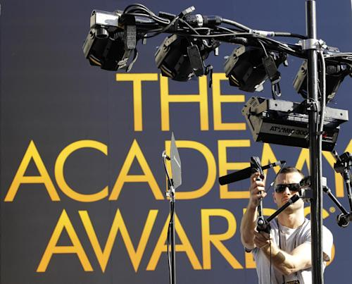 Max Muehlen hangs a microphone on a light stand overlooking the red carpet arrivals area outside the Kodak Theatre in preparation for the 84th Academy Awards in Los Angeles on Friday, Feb. 24, 2012.  The Oscars will be held on Sunday. (AP Photo/Amy Sancetta)