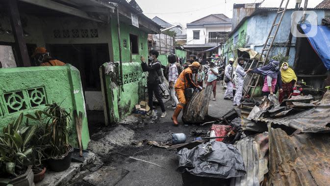 Warga dan petugas membersihkan sisa kebakaran di permukiman padat Kelurahan Bali Mester, Jatinegara, Jakarta, Selasa (8/9/2020). Kebakaran di permukiman padat itu melalap 11 rumah tinggal warga serta satu unit bengkel dan mengakibatkan 60 orang mengungsi. (Liputan6.com/Johan Tallo)